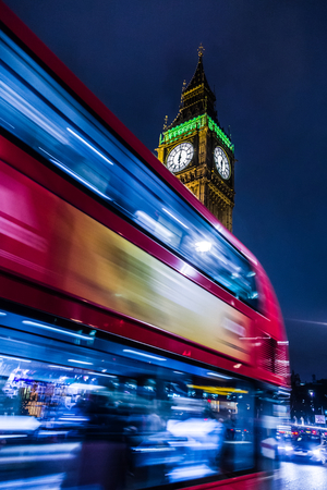 swiftly: Night at the streets of London, a british bus passing swiftly in front of Big Ben.