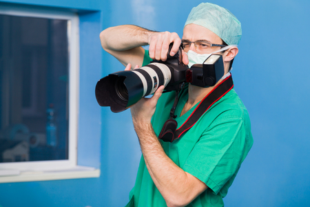 documenting: Young doctor photographing the medical procedures during surgery.