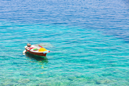 mediterranea: Beautiful colorful fishing boat floating lonly on the blue and turquoise water of the Mediterranea sea.