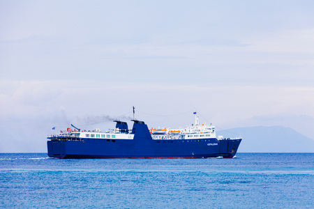 blue waters: Big cargo ship and ferry boat in the blue waters of the ocean.