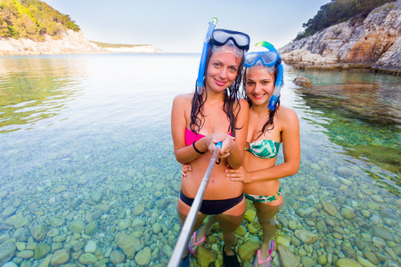 water sports: Two young women friends taking a selfportrait with a selfie stick in the Mediterranean sea.