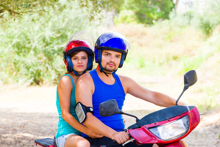 motor scooter: Young couple on a motor scooter ready to hit the road. Stock Photo