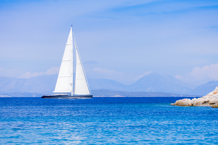 sailing boats: Hybrid luzury yacht swimming towards the shore, ready to spend the night.
