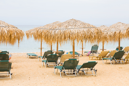 sun umbrellas: Dry exotic plants used to make sun umbrellas on a beach of the Mediterranean sea for sunbeds. Stock Photo