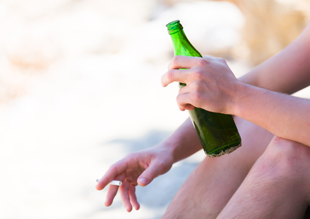 addiction drinking: Bad habits following to vacation - man drinking and smoking on the beach. Stock Photo