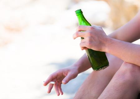 hombre tomando cerveza: Los malos hábitos siguientes para las vacaciones - hombre de consumición y fumar en la playa. Foto de archivo