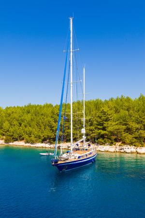 mediterranean forest: Shored yacht close to a mediterranean forest in the sea.