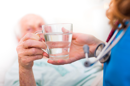 Elderly woman drinking water with the help of a nursing home caregiver.