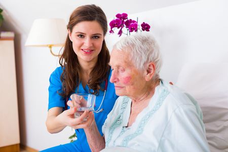 caring nurse: Caring nurse helping sick elderly woman to drink in bed in a nursing home. Stock Photo