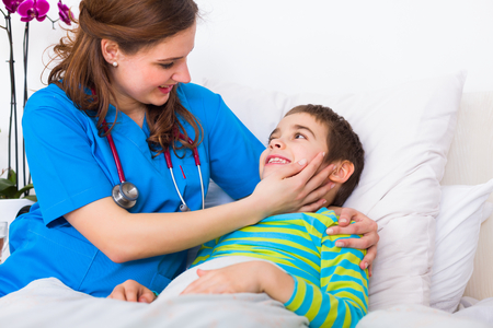 homecare: Little boy with young pediatrician doctor friend in the hospital smiling. Stock Photo
