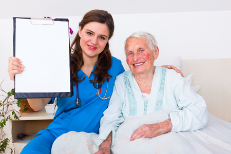 nursing record: Geriartric doctor showing a blank register to the camera with an elderly woman who got well from illness.