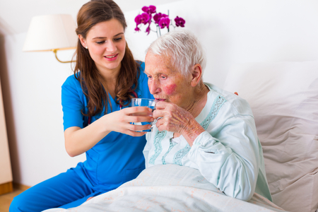 doctor giving glass: Kind geriatric doctor bringing water to the senior woman in need.