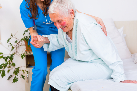 caring nurse: Caring nurse supporting her patient when she is getting up from bed after long time of illness. Stock Photo