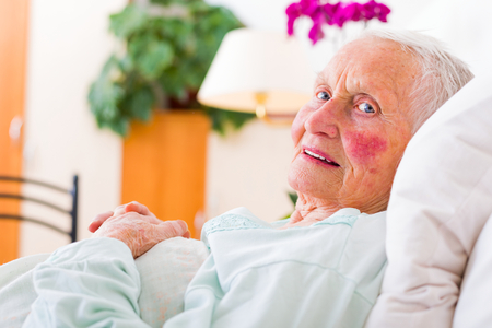 disease patients: Elderly patient laying in bed in a nursing home waiting for the doctor.