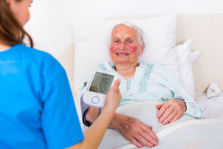 homecare: Elderly woman laying in bed at home, having her blood pressure measured by her homecare caretaker.