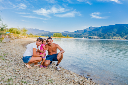 dad and daughter: hapy family next to a mountin lake hiking and having fun.