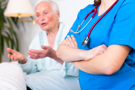 geriatrician: Confident geriatric doctor with stethoscope next to a talking elderly woman in hospital.
