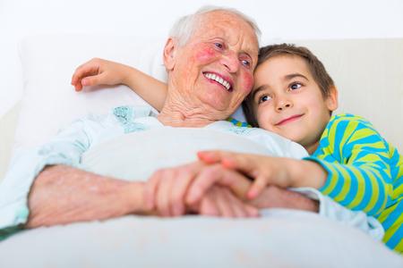 Sleepy Großmutter bereitet mit ihren liebevollen Enkelkind zu schlafen.