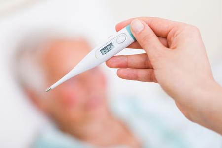 fiebre: Enfermera checkin la temperatura corporal del paciente enfermo - fiebre. Foto de archivo
