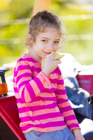 Little villager girl eating a tasty sandwoch on her grandfater 's tractor on the fields.