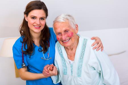 levantandose: Enfermera que cuida el apoyo a su paciente cuando ella es levantarse de la cama después de un largo tiempo de enfermedad. Foto de archivo