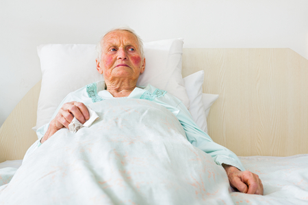 disease patients: Sick and sad elderly woman laying in bed in the nursing home.