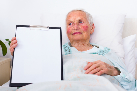 nursing record: A happy senior patient with a blank health register - clipboard - in her hands.