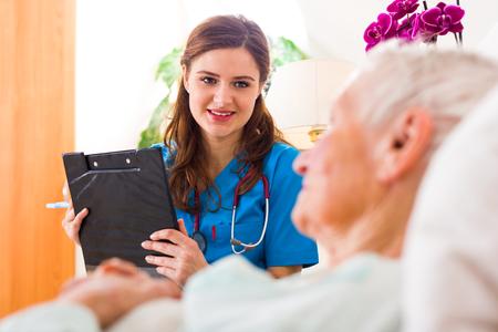 registering: Kind nurse with clopboard in her hands registering senior womans healthcare stats.