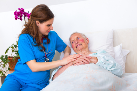 well equipped: Happy senior woman laying in bed in a well equipped luxury nursing home with a caring nurse supervising her 247.