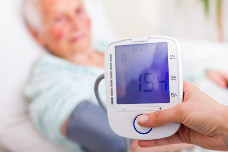 systolic: Caregiver measuring elderly womans systolic blood pressure in hospital.