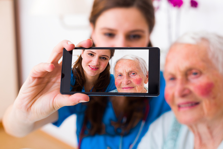 homecare: Beautiful doctor with a beautiful senior patient taking a selfie to send news to relatives from the hospital.