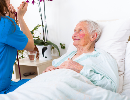 heart sounds: Young nurse examining an elderly woman with stethoscope, lustening to the lung and heart sounds. Stock Photo