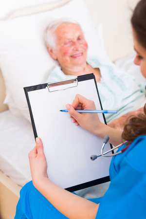 nursing record: Nurse writing on an empty sheet in the nursing home with a senior patient. Stock Photo