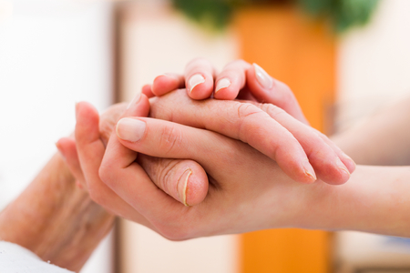 Senior vrouw in het verpleeghuis krijgt steun van een jonger persoon. Stockfoto