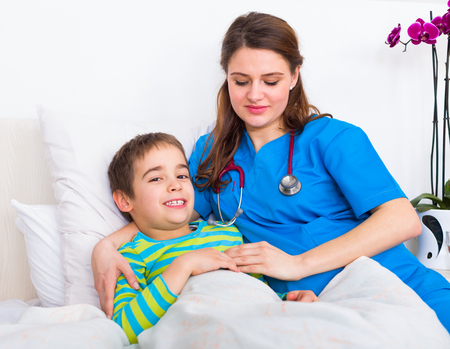 homecare: Pediatrician doctor caring for little boy in bed in the hospital.