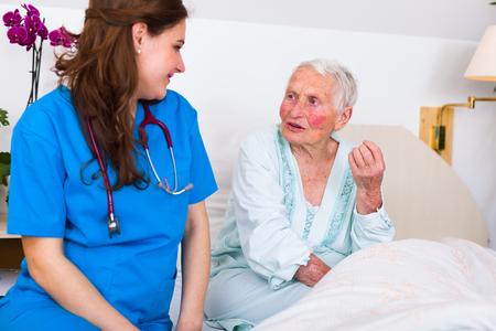 geriatrician: Patient nurse listening to elderly woman in bed in a nursing home.