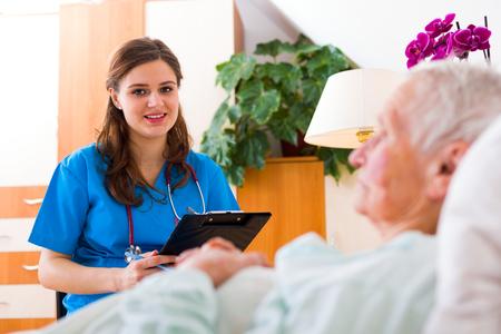 registering: Beautiful nurse visiting an elderly woman patient in the nursing home, registering her health status.