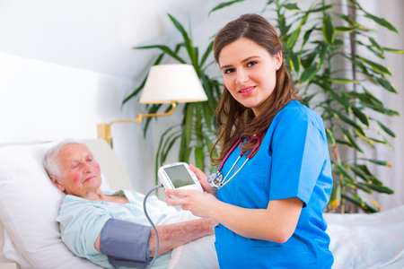 geriatric: Kind geriatric doctor measuring the blood pressure and heart rate of happy elderly patient.