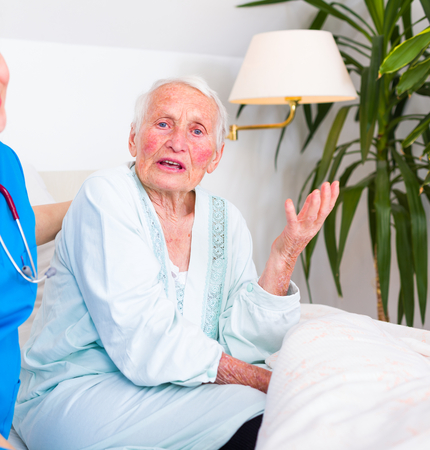 parkinson's: Sick senior woman talking to her doctor, explaining hardships.