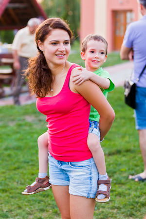 nurser: Beautiful young babysitter caring for and playing with a little boy. Stock Photo
