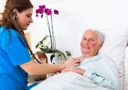 assisted: Happy elderly woman assisted by geriartric doctor, examination in the nursing home. Stock Photo
