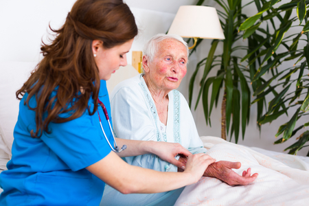 geriatrician: Senior woman talking, kind and patient doctor listening to her, examining her pulse. Stock Photo
