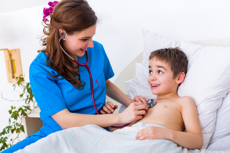Pediatrician doctor examining little boys heart beat and lungs to check for problems. Stock Photo