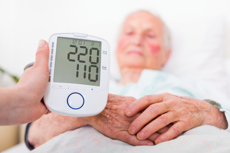 la presión arterial extremadamente alta registrada por la clínica de reposo médico geriatra - peligro de accidente cerebrovascular. Foto de archivo