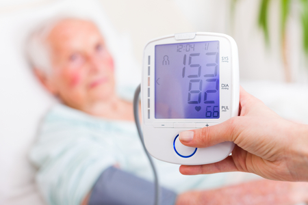 registering: Nurse registering sick elderly patients systolic and diastolic blood pressure in bed with the heart rate.