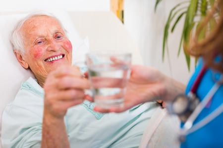 doctor giving glass: Elderly woman drinking water with the help of a nursing home caregiver.