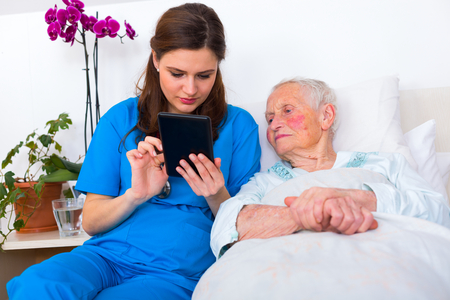 caring nurse: Caring nurse showing a digital tablet to an elderly woman in a nursing home.