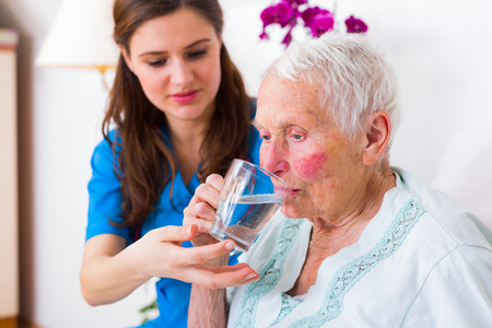 Caring nurse helping sick elderly woman to drink in bed in a nursing home. Banco de Imagens