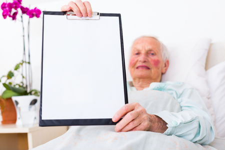 nursing record: Elderly woman showong an empty paper on a clipboard , laying in bed in a nursing home. Stock Photo