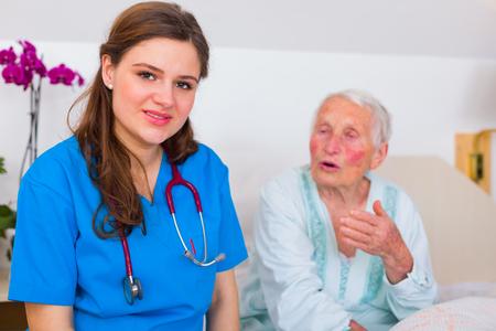 geriatrician: Patient nurse listening to senior woman in bed in a nursing home.